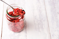 Super food goji berries in a metal spoon on a full jar. Royalty Free Stock Images
