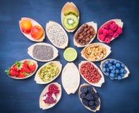 Super food ingredients, berries, fruits, nuts, seeds. Fruits, berries, nuts, seeds top view on dark background.Healthy, detox, super food ingredients concept stock photo