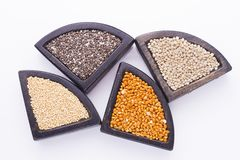 Super food. In wooden containers, amaranth, chia, quinoa and red millet royalty free stock photos