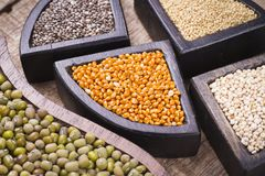Super food. In wooden containers, amaranth, chia, quinoa and red millet stock images