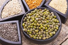 Super food. In wooden containers, amaranth, chia, quinoa and red millet stock photos