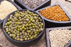 Super food. In wooden containers, amaranth, chia, quinoa and red millet royalty free stock image