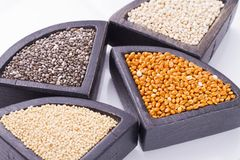 Super food. In wooden containers, amaranth, chia, quinoa and red millet royalty free stock photo