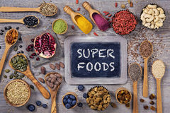 Super foods in spoons and bowls. On a wooden background royalty free stock images