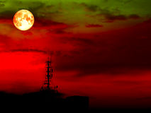 Super full blood moon and blur shadow signal pillar on roof Royalty Free Stock Images