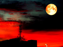 Super full blood moon and blur shadow signal pillar on roof Royalty Free Stock Photography