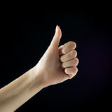 Super good. Thumb up. Female hand. Finger. Isolated on black background Royalty Free Stock Images