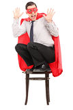 Super héroe aterrorizado que se coloca en una silla Imágenes de archivo libres de regalías