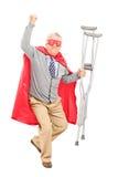 Super héroe con las muletas que gesticula felicidad Fotos de archivo