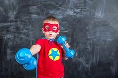 Super héroe del muchacho con pesas de gimnasia Imagen de archivo libre de regalías