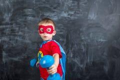 Super héroe del muchacho con pesas de gimnasia Foto de archivo libre de regalías