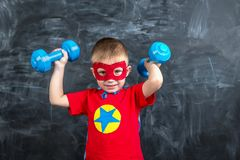 Super héroe del muchacho con pesas de gimnasia Fotos de archivo libres de regalías