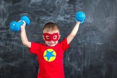 Super héroe del muchacho con pesas de gimnasia Fotos de archivo
