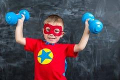 Super héroe del muchacho con pesas de gimnasia Imagen de archivo