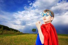 Super héroe divertido hermoso del niño que lleva un cabo que se coloca en un campo verde del verano Fotografía de archivo