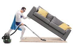 Super héroe fuerte que limpia con la aspiradora debajo de un sofá Fotos de archivo libres de regalías