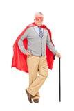 Super héroe mayor que presenta con un bastón Fotos de archivo libres de regalías