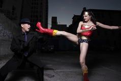 Super héroe que golpea al bandido con el pie malvado fotografía de archivo