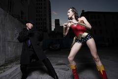 Super héroe que lucha al bandido imagen de archivo