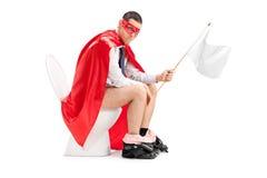 Super héroe que sostiene una bandera blanca asentada en retrete Fotos de archivo libres de regalías