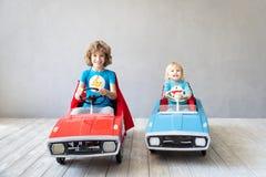 Super héroes de los niños que juegan en casa foto de archivo