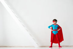 Super héros d'enfant dans un manteau rouge Photo stock