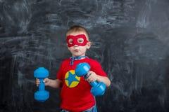 Super héros de garçon avec des haltères Photos libres de droits