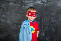 Super héros de garçon dans un masque rouge de cap bleu et un T-shirt rouge avec une étoile Photographie stock