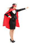 Super héros féminin tenant son poing dans le ciel Photos stock