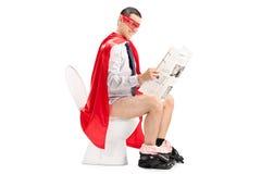 Super héros lisant les actualités posées sur une toilette Photo stock