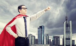 Super héros se tenant devant une ville foncée Photographie stock