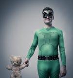 Super héros vert tenant un ours de nounours Photographie stock