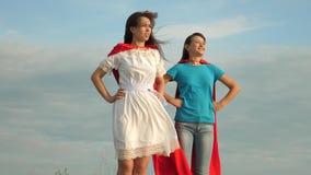 Super h?roes del juego de la mam? y de la hija dos muchachas en capas rojas de super héroes se oponen a un cielo azul, el viento  metrajes