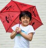 A super happy child carrying umbrella; casual portrait