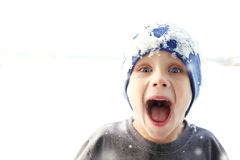 Super Happy Kid Outside in Winter Snow. A super happy kid with a big smile is wearing an ice covered stocking cap as he plays outside in the winter snow Royalty Free Stock Photography