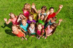Super happy large group of kids. Large group of happy kids, boys and girls, about 10 years old standing on the green grass top view Royalty Free Stock Photo