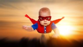 Super-herói pequeno do superman do bebê da criança com um th vermelho do voo do cabo imagens de stock