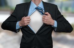Super Hero. Businessman tearing his shirt and suite open with both hands. Showing the white shirt under it Stock Photos