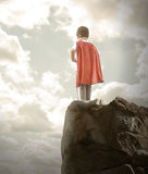 Super Hero Boy Ready to Fly. A young super hero boy is wearing a red cape and standing on a rocky cliff looking at a cloudy sky with copyspace Stock Photo