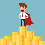 Super hero businessman standing on  money stack. Royalty Free Stock Image