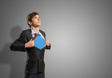Super hero. Businessman tearing his shirt under her blue clothes super hero stock photos