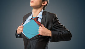 Super hero. Businessman tearing his shirt under her blue clothes super hero stock image