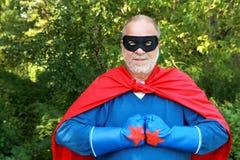 Super hero. Confident senior super hero kiking fist together Stock Photos
