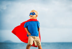 Super Hero flying in he sea. Super Hero Kid smiling with a goggles in the eye Royalty Free Stock Image