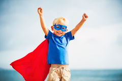 Super Hero flying in he sea. Super Hero Kid smiling with a goggles in the eye Stock Image