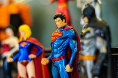 Super Hero Iconic Figurines. Iconic figurines of Superman in focus looking directly at you and also Batman, Supergirl and Wonder Woman comic characters on a Royalty Free Stock Photo