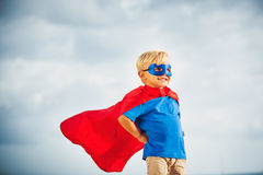 Super Hero kid with a mask flying. Super Hero Kid in red blue dress by the ocean stock images