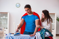 The super hero man husband ironing at home helping his wife Royalty Free Stock Image