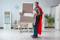 The super hero moving furniture at home Stock Images