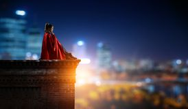 Super hero on roof. Mixed media. Thoughtful woman in cape sitting on top of building. Mixed media stock image